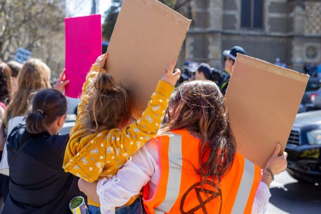 mother and daughter holding posters at an XR ralley